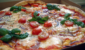 Pizza med mozarella, färska tomater och rödlök