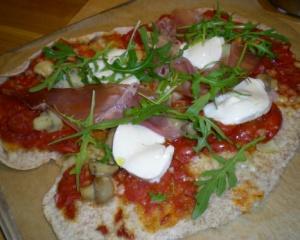 Pizza med lufftorkad skinka, ruccola och mozarella